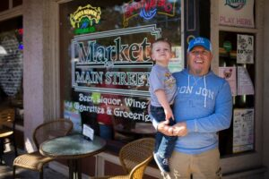 man and kid standing outside of shop