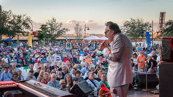 man playing harmonica on stage at bradenton blues festival