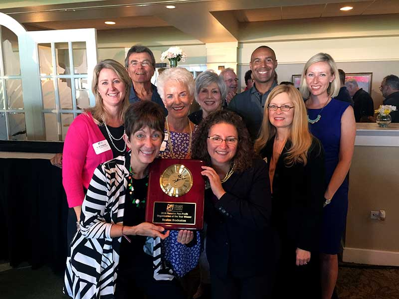 Realize Bradenton board, staff, and volunteers smiling with award